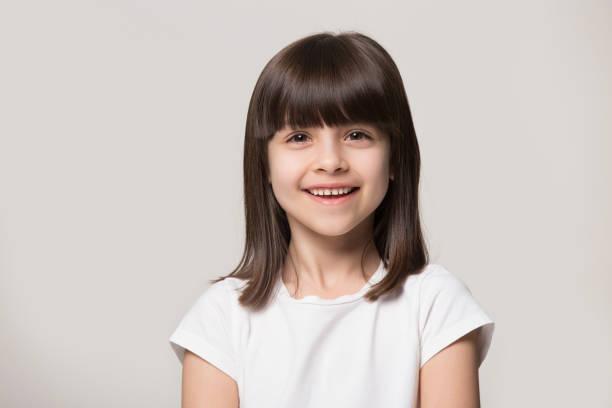 headshot portret van gelukkig meisje dat in studio stelt - alleen één meisje stockfoto's en -beelden
