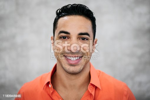 Close-up headshot of mid adult Latin American businessman with positive attitude wearing open collar button up orange shirt against gray background.
