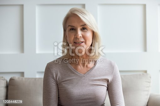 Close up headshot portrait of senior positive woman sit on couch look at camera smiling and posing, optimistic mature female talk on video call, having pleasant conversation using modern technologies