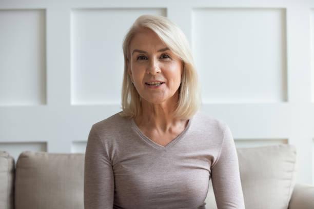 headshot portrait of mature woman sit on couch talking - webcam portrait стоковые фото и изображения