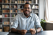 Headshot portrait of happy african American man in glasses sit at desk have video call on gadget, smiling biracial young male in spectacles talk speak on web, using online dating service application