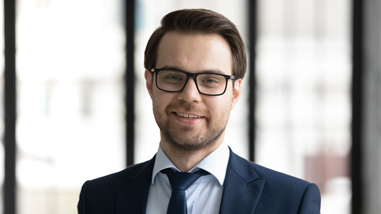 825082848 istock photo Headshot portrait of smiling businessman in glasses at workplace 1248226404