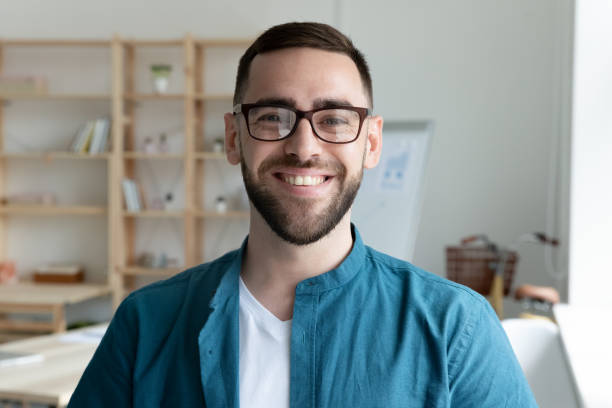 Headshot portrait of smiling male employee in office stock photo