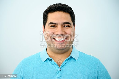Close-up of cheerful Latin American man in his early 40s wearing a turquoise polo shirt against a light blue background and looking at camera.