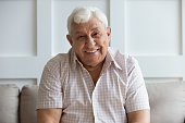 istock Headshot portrait of smiling mature man relaxing on sofa 1205448227