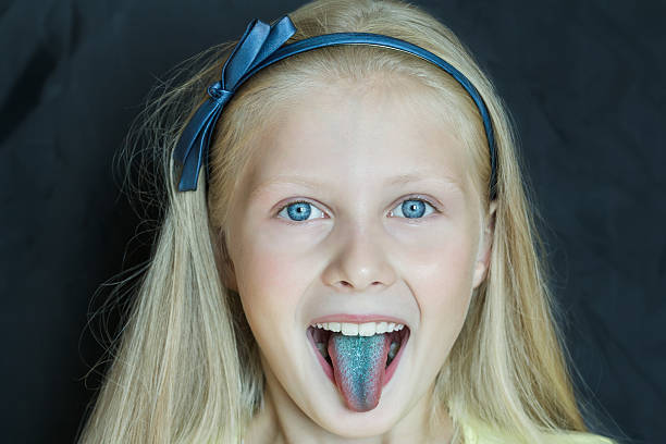 headshot portrait of teenage blonde girl with sticking out tongue - tongue stock photos and pictures