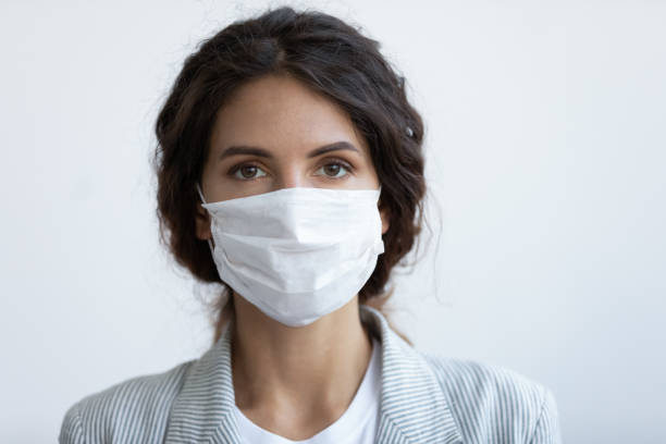 Headshot portrait woman wear face mask protecting from COVID19 stock photo