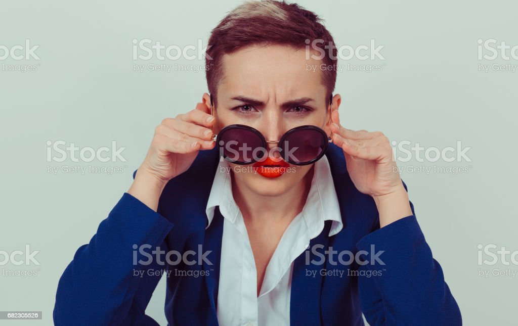 Headshot serious angry bitchy woman wife holding sunglasses down skeptically looking at you isolated green yellow wall background, blue shirt. Human face expression body language, attitude, perception stock photo