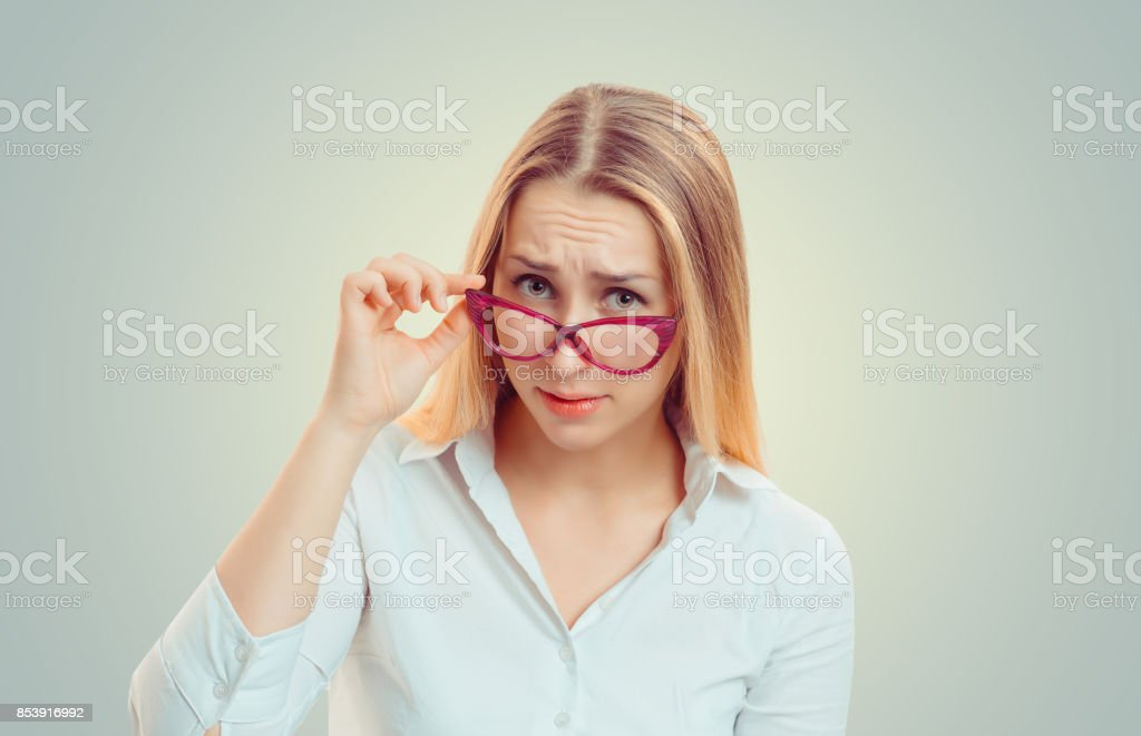 Headshot serious angry bitchy woman wife holding sunglasses down skeptically looking at you isolated green yellow wall background, white shirt. Human face expression body language, attitude perception stock photo