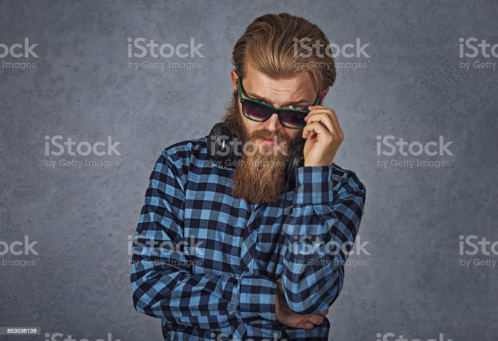 Headshot serious skeptical angry man wife holding sunglasses down skeptically looking at you isolated grey gray wall background blue black shirt Human face expression body language attitude perception stock photo