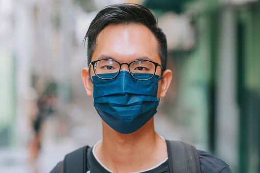 headshot Young Asian chinese man wearing protective face mask to prevent the spread of viruses in the city during the epidemic of Covid-19 health crisis