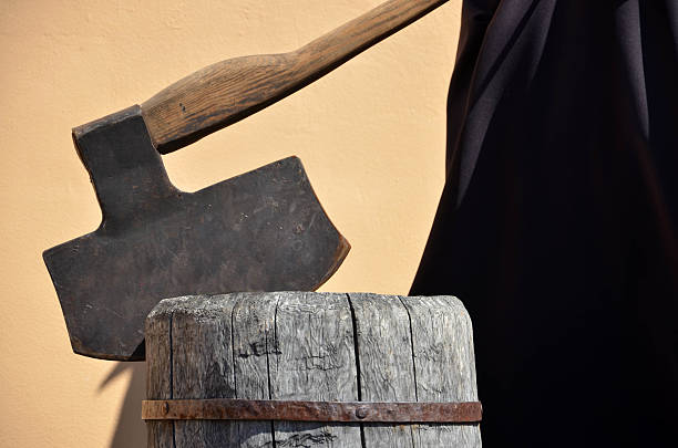 Headsman's axe hewed in old wooden chunk stock photo