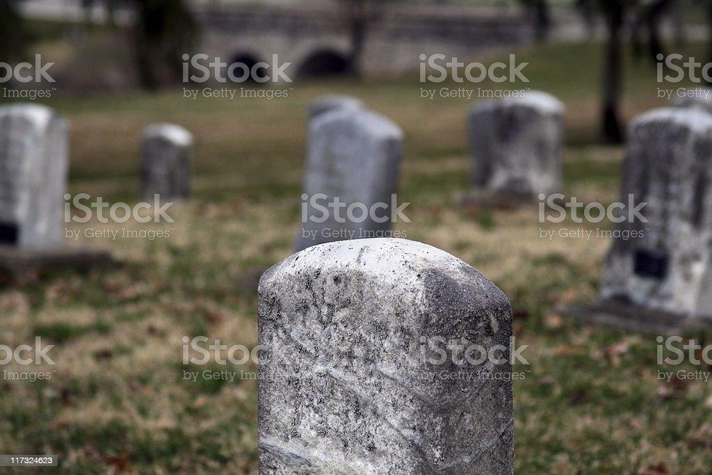 Headsone in Creepy Cemetery with Bridge in background stock photo