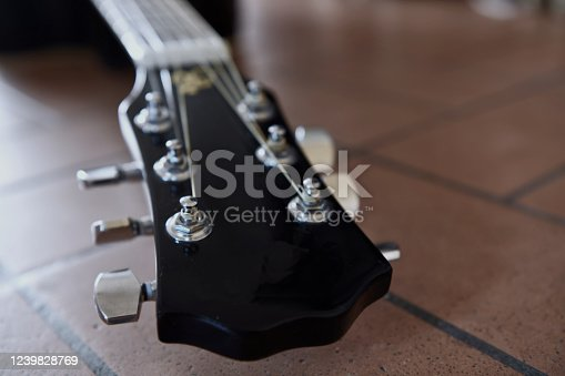 1014432572 istock photo Headstock and tuners of beautiful black acoustic guitar lying on the brick floor closeup. Concept of vintage style. 1239828769