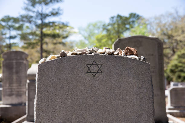 Headstone in Jewish Cemetery with Star of David and Memory Stones Headstone in a Jewish cemetery with Star of David and memory stones.  Selective focus on the foreground.  Copy space. judaism stock pictures, royalty-free photos & images