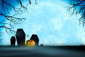 A trio of headstones are silhouetted by the rising full moon.  A colony of bats flies in the distance and a jack o'lantern sits in a foggy mist that hugs the ground in front of the tombstones.