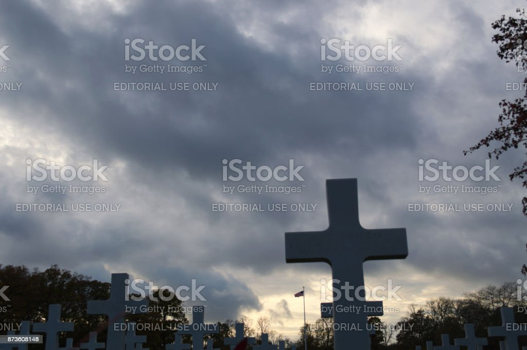 Headstones with USA flag in far background stock photo