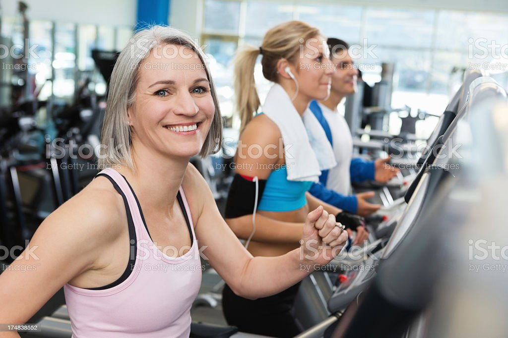 Healhty mature woman walking on treadmill in gym stock photo