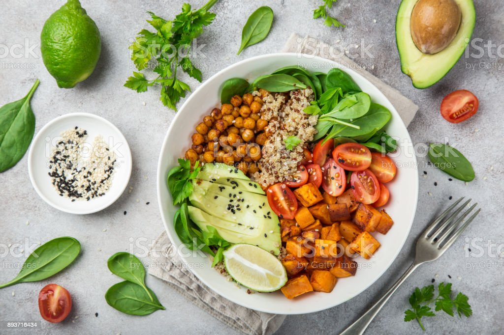 healhty vegan lunch bowl. Avocado, quinoa, sweet potato, tomato, spinach and chickpeas vegetables salad