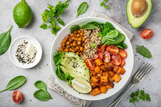 healhty vegan lunch bowl. Avocado, quinoa, sweet potato, tomato, spinach and chickpeas vegetables salad stock photo