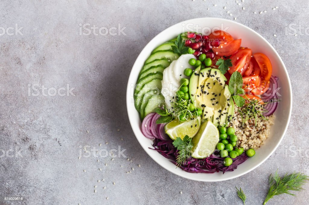 healhty vegan lunch bowl. Avocado, quinoa, tomato, cucumber, red cabbage, green peas and radish  vegetables salad. stock photo