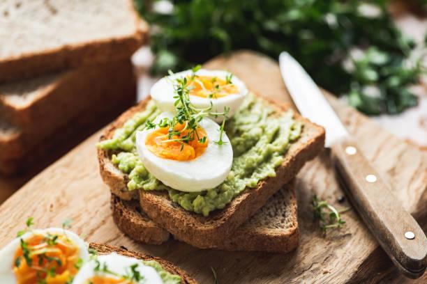 desayuno saludable tostadas con aguacate, huevo - desayuno fotografías e imágenes de stock