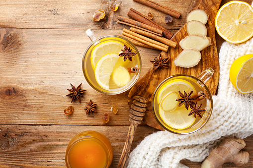 istock Healing ginger tea in two glass mug in scarf with lemon, honey and spices. Autumn hot drink on rustic wooden table top view. 1171555144