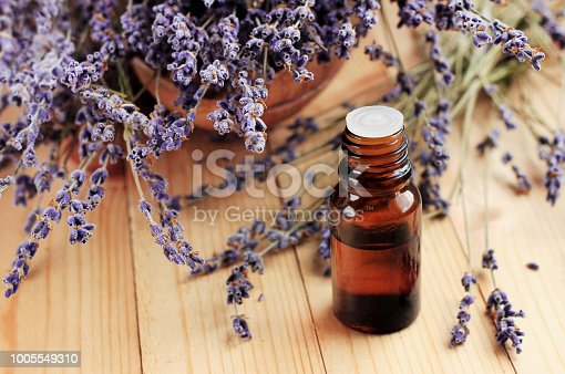 Dried purple plant flowers, dark glass dropper bottle, wooden table. Natural aromatherapy.