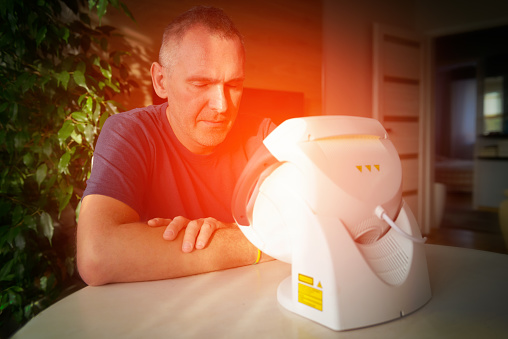 Man treating pain in the sinuses and head with infrared light therapy. The man sits at the table near the healing lamp.