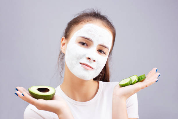 Health and beauty. Facial skin care. Young girl makes a moisturizing cleansing face mask stock photo
