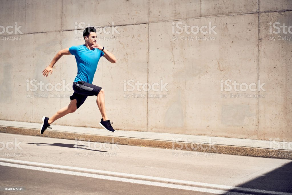Health and fitness concept. Man doing sprinting and jumping exercises during workout session in the city stock photo