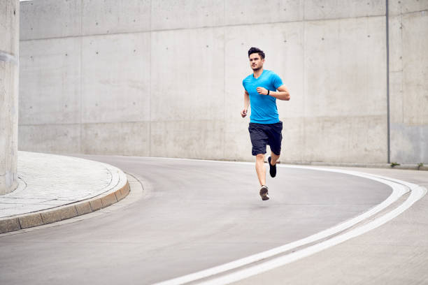 Health and fitness concept. Muscular man jogging in the city during workout session stock photo
