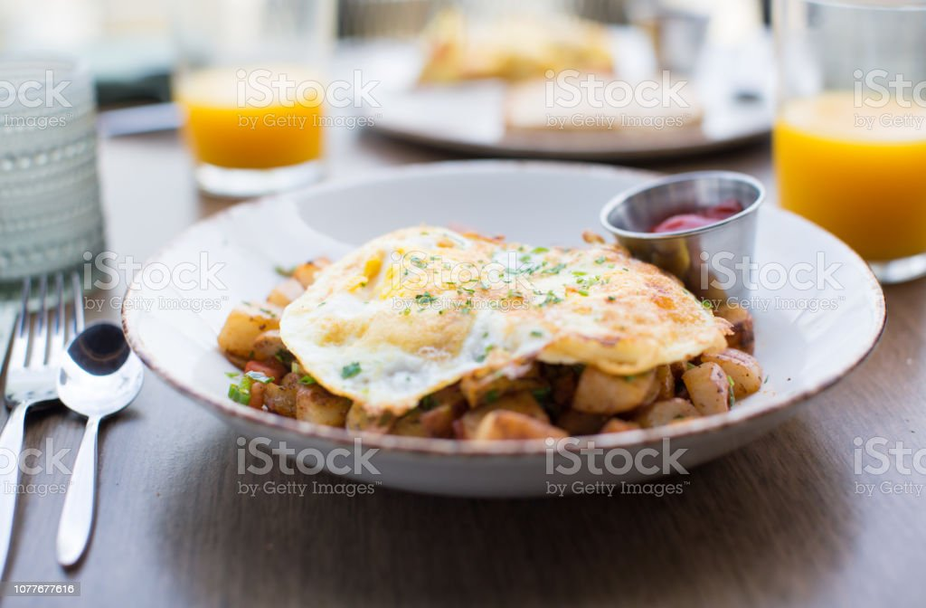 Health and Fitness Cooking. Breakfast on a Plate with Eggs, Potatoes, Green Onion,Ketchup, Orange Juice, Bread. Delicious Meal on Table. Fried Egg and Grilled Potatoes. Big Meal. Healthy Diet. stock photo