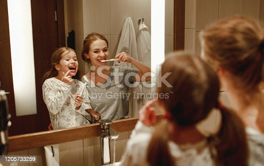 istock health and hygiene of the oral cavity. mother and child daughter brush their teeth in   bathroom in front of a mirror 1205733259