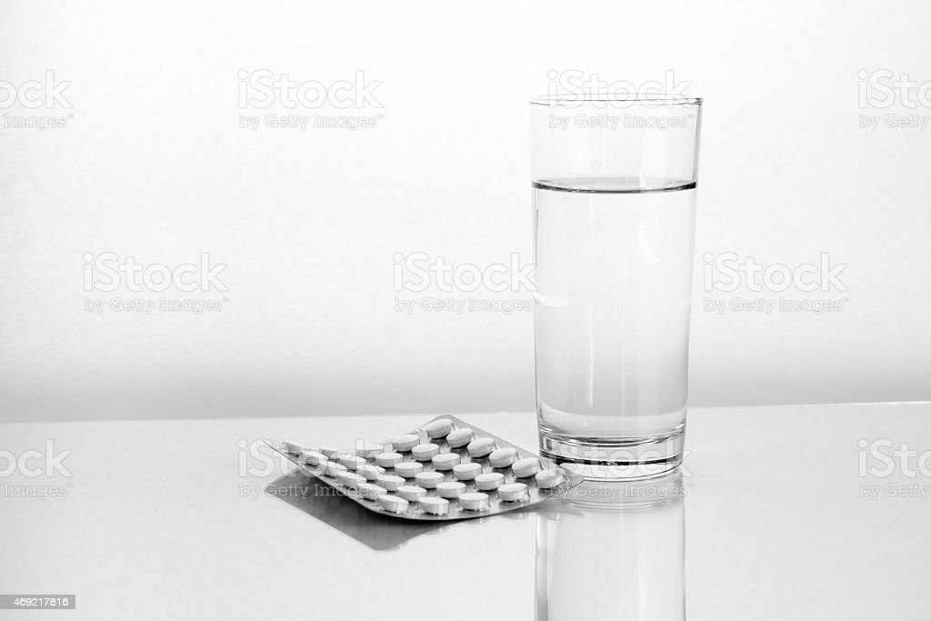 Health and medication. Pills and glass of water. stock photo