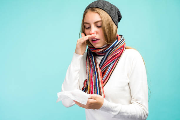 Health and medicine concept - Sad Teen Girl blowing nose into tissue, on a blue background. Pretty girl cold with snot. Health and medicine concept - Sad Teen Girl blowing nose into tissue, on a blue background. Pretty girl cold with snot. - image mucus stock pictures, royalty-free photos & images