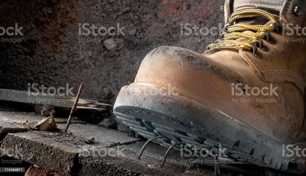 Health and safety Dirty work boots stepping on a nail stock photo