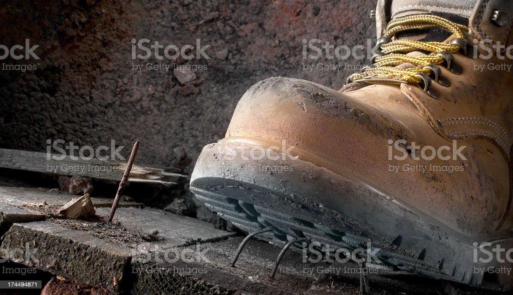 Gesundheit und Sicherheit schmutzig Arbeitsstiefel Schritt an einem Nagel – Foto