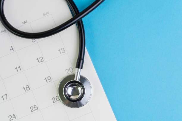 hälso-och sjukvård och medicinsk tentamen schema kalender, påminnelse eller utnämning koncept, läkarens stetoskop på vit ren kalender med datum på blå bakgrund med kopia utrymme - calendar workout bildbanksfoton och bilder