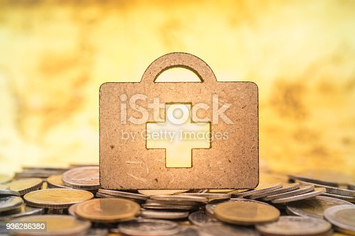 istock Health Care and money concept. Close up of wooden bag shape with red cross symbol on pile od coins. 936286380