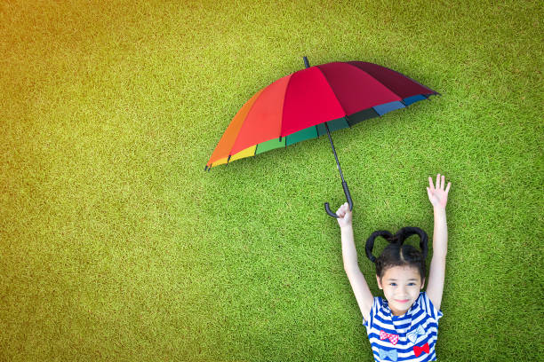 Health care assurance, family and children life insurance medical healthcare business concept with happy asian girl kid holding umbrella uv protection safety from sunlight ray on sunny day Health care assurance, family and children life insurance medical healthcare business concept with happy asian girl kid holding umbrella uv protection safety from sunlight ray on sunny day environmental consciousness stock pictures, royalty-free photos & images