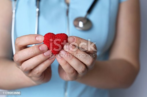 istock Health care, cardiology, woman doctor with stethoscope holding red knitted heart in hands 1128953886