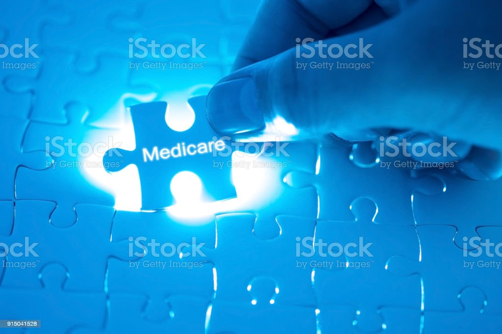 Health Care Concept. Doctor holding a jigsaw puzzle with medicare word. stock photo