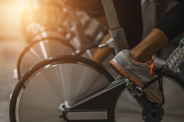 Health care concept Young People - group of women and men - doing sport biking in the gym for fitness .Health care concept exercise bike stock pictures, royalty-free photos & images