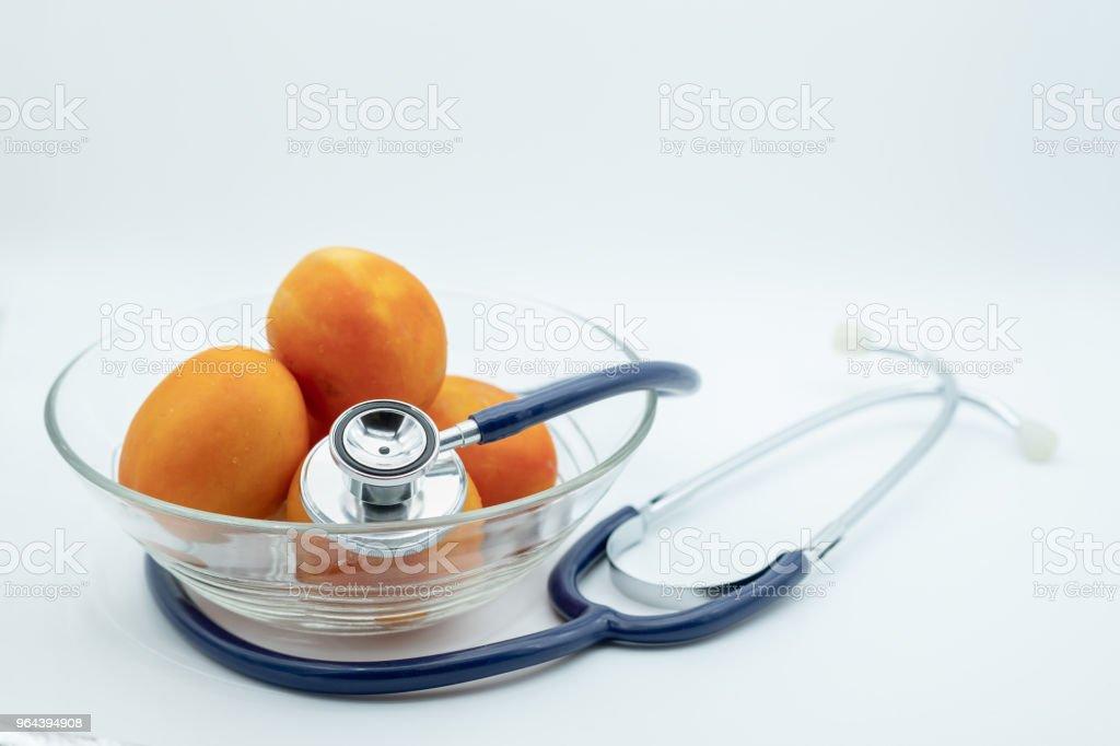 Conceito de cuidados de saúde. Estetoscópio com tomate fresco na tigela de vidro em fundo branco. - Foto de stock de Alimentação Saudável royalty-free
