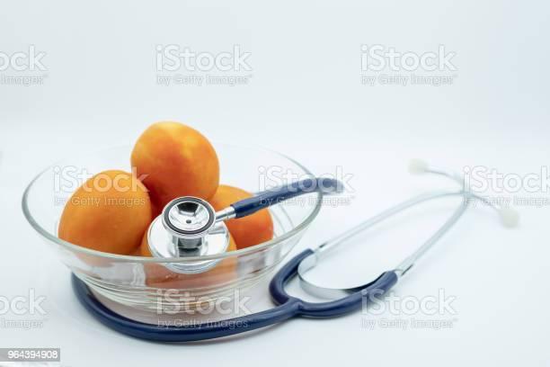 Foto de Conceito De Cuidados De Saúde Estetoscópio Com Tomate Fresco Na Tigela De Vidro Em Fundo Branco e mais fotos de stock de Alimentação Saudável