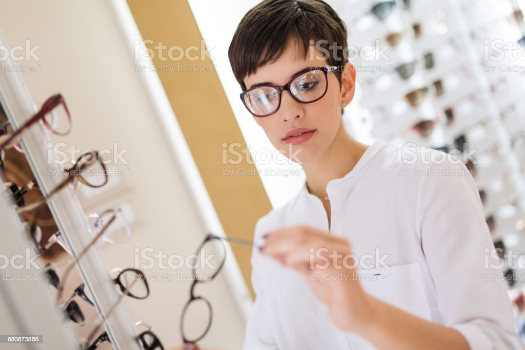health care, eyesight and vision concept - happy woman choosing glasses at optics store royalty-free stock photo