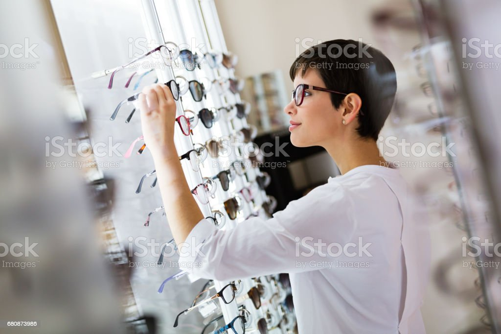 health care, eyesight and vision concept - happy woman choosing glasses at optics store stock photo