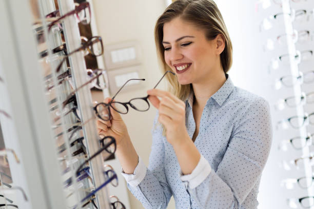 health care, eyesight and vision concept - happy woman choosing glasses at optics store health care, eyesight and vision concept - happy beautiful woman choosing glasses at optics store serbia and montenegro stock pictures, royalty-free photos & images