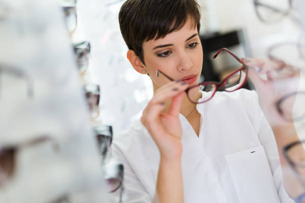health care, eyesight and vision concept - happy woman choosing glasses at optics store - sale lenses stock photos and pictures